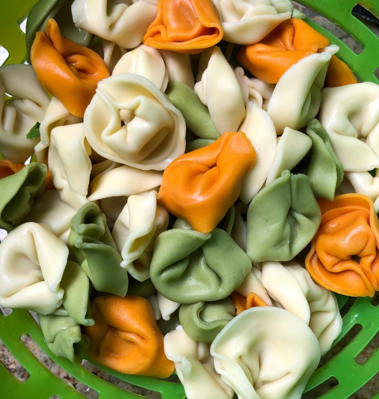 Multicolored tortellini draining in a colander for pasta salad