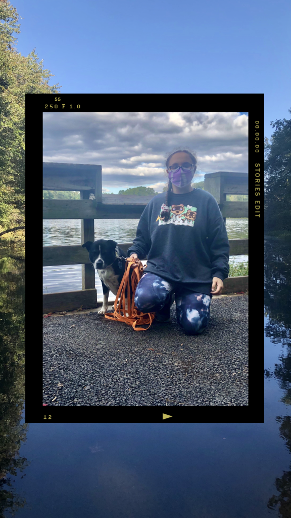 girl and dog in front of lake