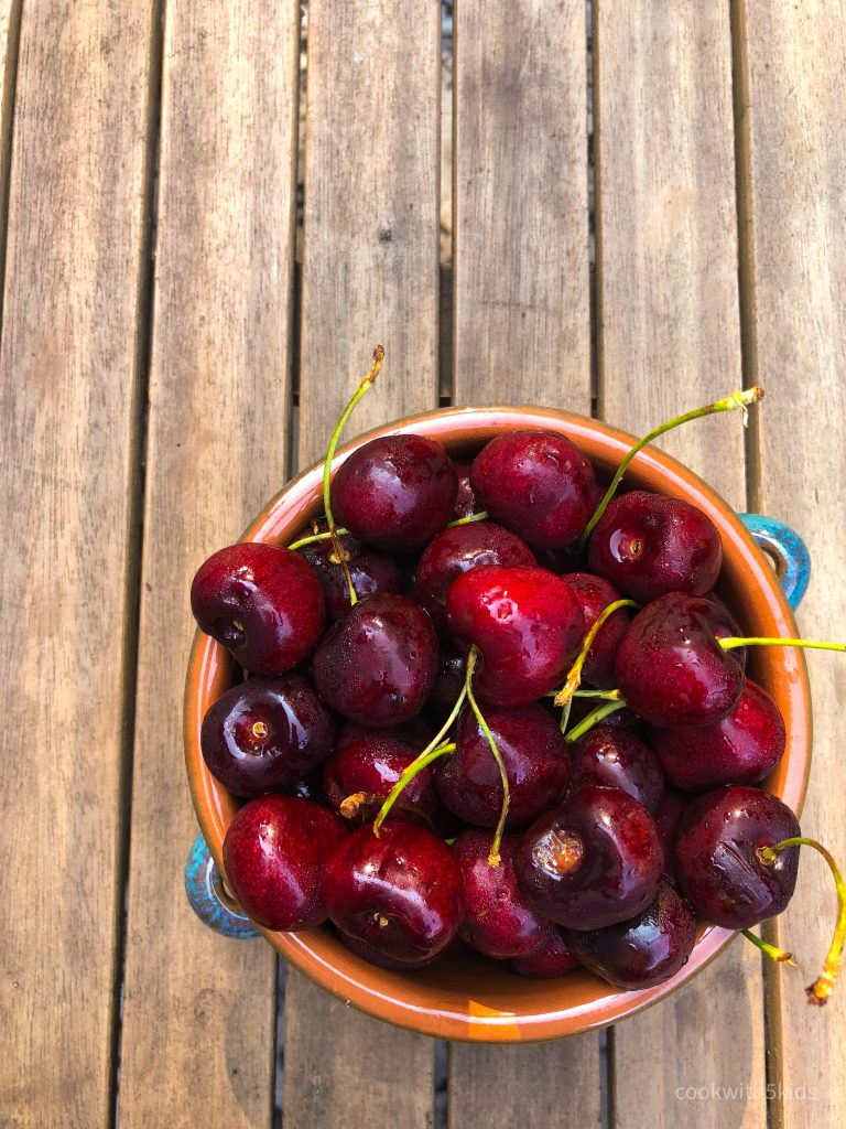 bowl of cherries sitting on a table