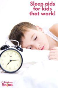 boy sleeping with alarm clock next to him