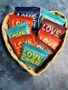 heart shaped basket holding vegan love corn snacks