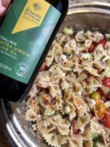pot with pasta salad in it and olive oil in the foreground