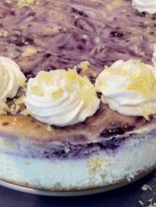 blueberry lemon cheesecake with whipped cream and lemon sugar